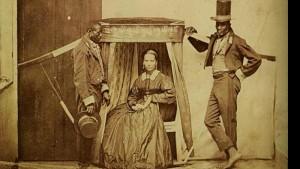 """Foto do século XIX, na Bahia, conhecida como """"A dama da liteira"""", com uma senhora branca emoldurada no seu transporte, por dois escravos (Reprodução)"""