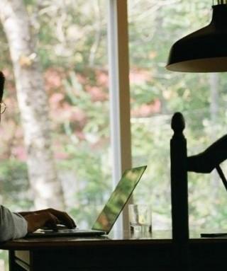 Imagem de um homem tentando escrever no notebook, olhando à janela, copo com água, óculos,